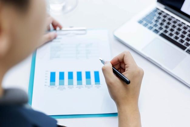 Koncepcja partnerów biznesowych młody biznesmen trzymający pióro wskazujące na podsumowanie zysków z ostatniego miesiąca w formie dokumentów.