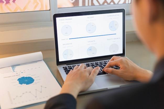 Koncepcja partnerów biznesowych młody biznesmen za pomocą laptopa, weryfikując roczne podsumowanie sprzedaży.