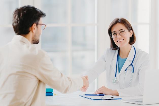 Koncepcja partnerstwa, pomocy, zaufania i medycyny. lekarka podaje dłoń wdzięcznemu pacjentowi za dobre leczenie i profesjonalizm, pozuje w klinice, dokumentacja medyczna w pobliżu białego stołu