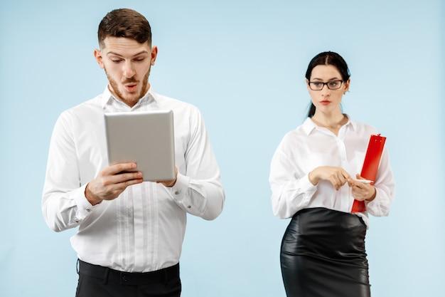 Koncepcja partnerstwa w biznesie. młody emocjonalny mężczyzna i kobieta na niebieskim tle w studio. ludzkie emocje i koncepcja partnerstwa