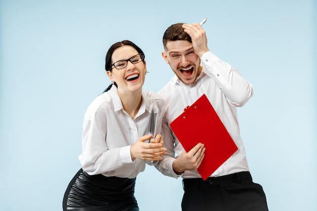Koncepcja partnerstwa w biznesie. młody szczęśliwy uśmiechnięty mężczyzna i kobieta stojąca na niebieskim tle w studio