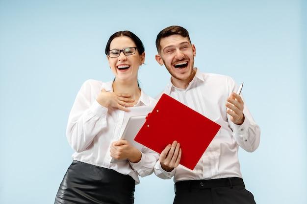 Koncepcja partnerstwa w biznesie. młody szczęśliwy uśmiechnięty mężczyzna i kobieta stojąca na niebieskim tle