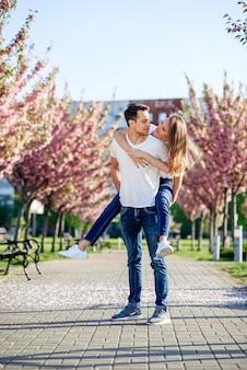 Koncepcja pasji i miłości. mężczyzna i kobieta całuje się w kwitnącym ogrodzie w wiosenny dzień.
