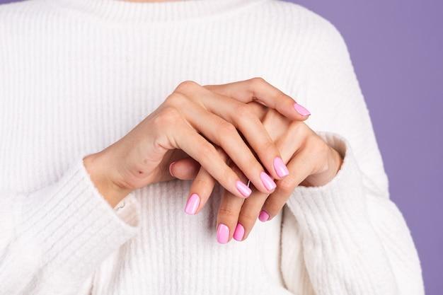 Koncepcja paznokci uroda, drobny różowy wiosenny kolor manicure biały sweter fioletowa ściana