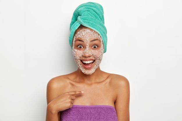 Koncepcja peelingu i oczyszczania. zadowolona radosna kobieta wskazuje na siebie ze zdumieniem i radosną reakcją, pyta o mnie, ma peeling na twarzy, kąpie się, lubi zabiegi higieniczne