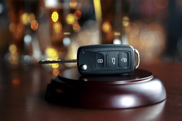 Koncepcja picia i jazdy. kluczyk na drewnianym stole, tło pubu