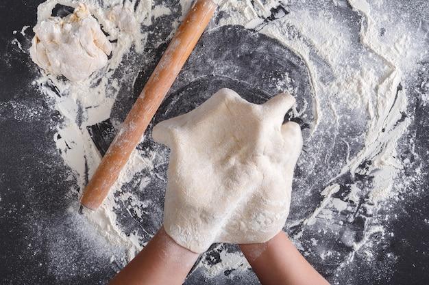 Koncepcja pieczenia. cienkie ciasto ręcznie robione. gotowanie rąk