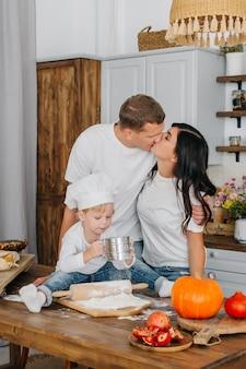 Koncepcja pieczenia domowej roboty. rodzice całują się, a mały słodki chłopiec bawi się mąką w kuchni.