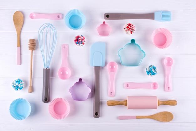 Koncepcja pieczenia i gotowania. wzór wykonany z foremek do ciastek, trzepaczki, wałka i narzędzi kuchennych do wyrobu słodyczy. białe tło. widok z góry na wakacje martwa pieczenia