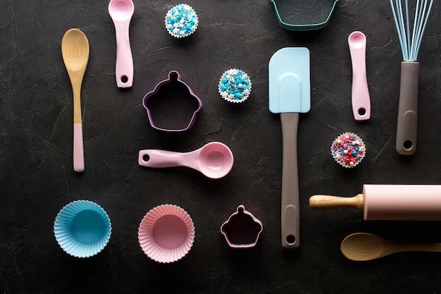 Koncepcja pieczenia i gotowania. wzór wykonany z foremek do ciastek, trzepaczki, wałka i narzędzi kuchennych do wyrobu słodyczy. ciemne tło. widok z góry na wakacje martwa pieczenia