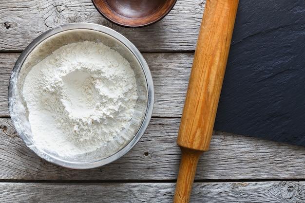 Koncepcja pieczenia. mąka i wałek do ciasta na rustykalne drewno widok z góry