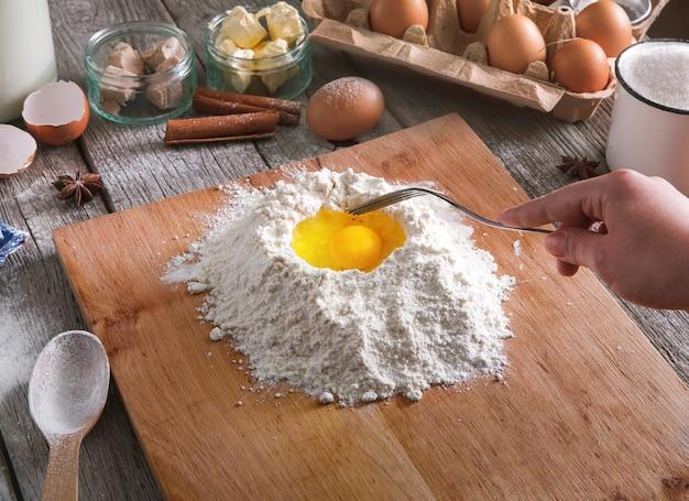 Koncepcja pieczenia. mąka, mleko, masło, drożdże, przyprawy i jajka karton na rustykalnym drewnianym stole, składniki do gotowania. nie do poznania kobiece dłonie w widoku pov mieszają ciasto. kobieta piekarz