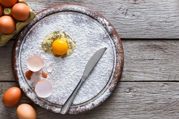 Koncepcja pieczenia. posyp mąkę i jajka na drewnianej desce do krojenia w pobliżu noża, składniki do gotowania. przygotuj się do zrobienia ciasta drożdżowego. widok z góry