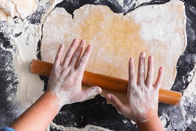 Koncepcja pieczenia. ręce widok z góry rozwałkować ciasto.