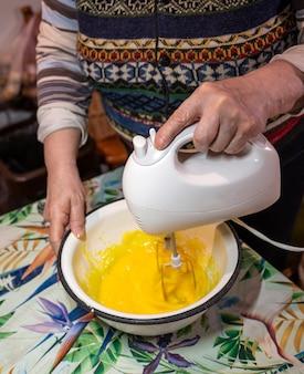 Koncepcja pieczenia. starszy kobieta piecze domowe ciasto w domu