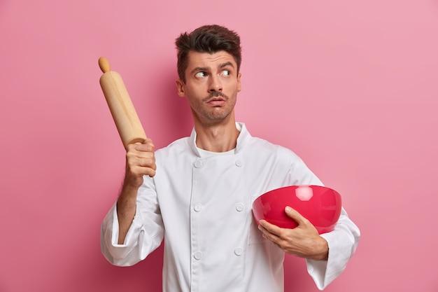 Koncepcja piekarni i gotowania. zamyślony, zaskoczony kucharz trzyma drewniany wałek do ciasta i miskę