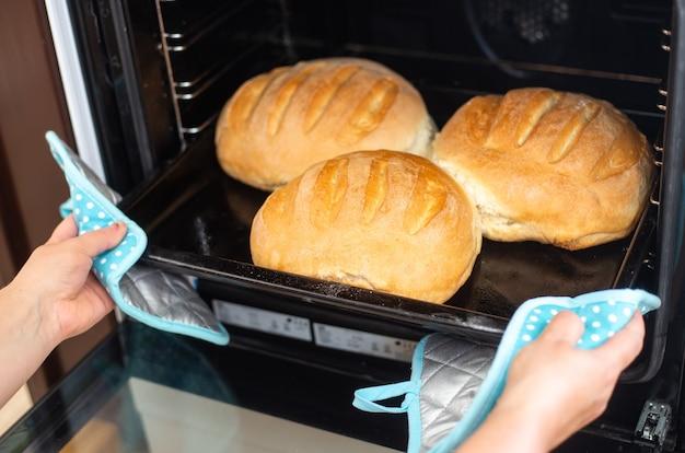 Koncepcja piekarni, kobieta upiekła domowy tradycyjny chleb pełnoziarnisty podczas kryzysu gospodarczego, braku jedzenia