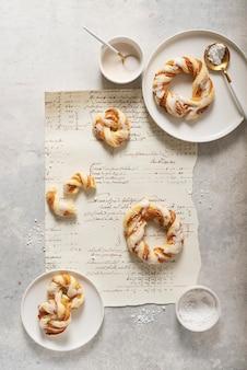 Koncepcja piekarni, słodkie okrągłe desery z glazurowanym cukrem na jasnej powierzchni. widok z góry na dół.