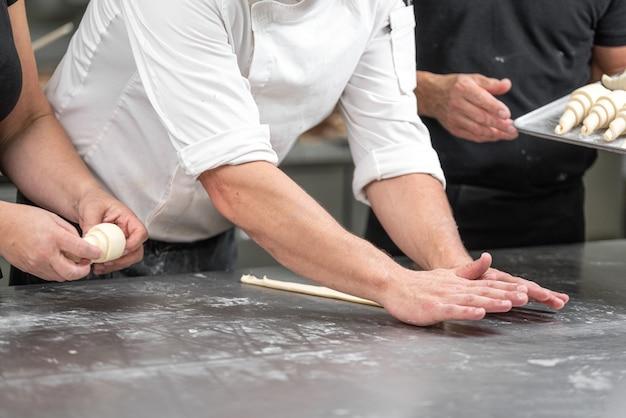 Koncepcja piekarza. zrób rogalika na stole, świeżej piekarni.