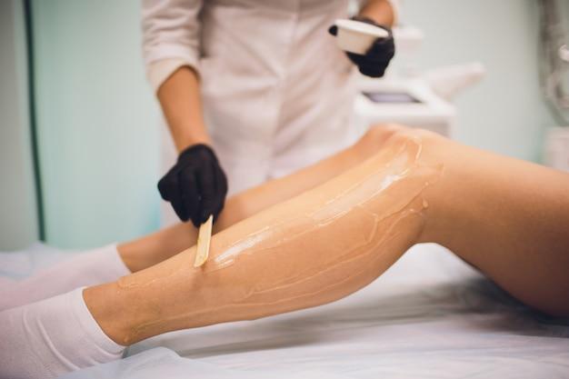 Koncepcja piękna, depilacji, depilacji, depilacji i ludzi - piękna kobieta z aplikatorem nakładającym wosk do depilacji na nogę.