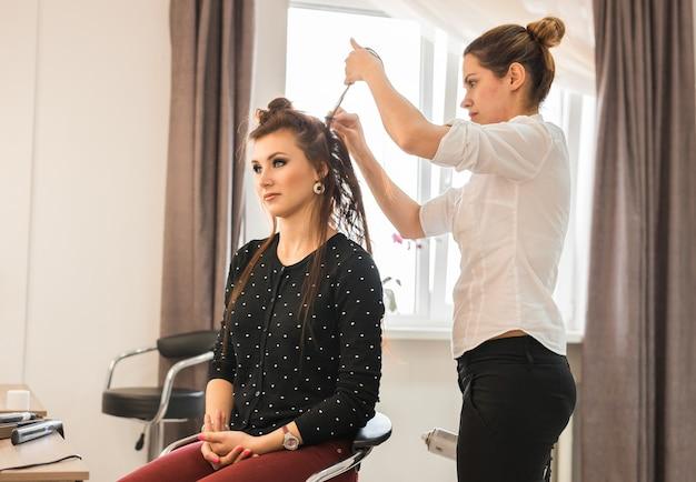 Koncepcja piękna i ludzi szczęśliwa młoda kobieta z fryzjerem w salonie fryzjerskim