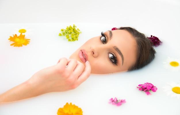 Koncepcja piękna i spa rozpieszczanie skóry i ciała. piękna kobieta o czystej skórze i pięknym makijażu w wannie z mlekiem z pływającymi kwiatami.