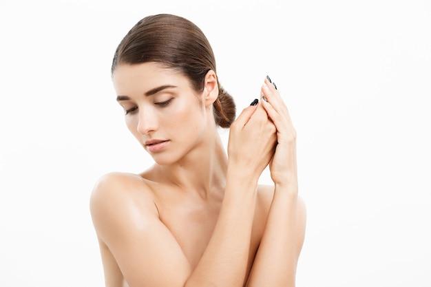 Koncepcja piękna i spa - urocza młoda kobieta z idealnie czystą skórą na białej ścianie.