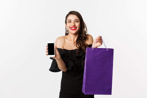 Koncepcja piękna i zakupów. piękna i stylowa kobieta pokazująca ekran telefonu komórkowego i torbę, kupująca online, stojąca na białym tle