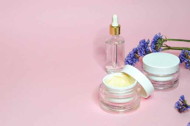 Koncepcja piękna. naturalne kosmetyki do codziennej pielęgnacji skóry w szklanym słoju na różowym tle. produkt krem i serum przeciw zmarszczkom, przeciwstarzeniowe, liftingujące, odświeżające, oczyszczające, nawilżające.