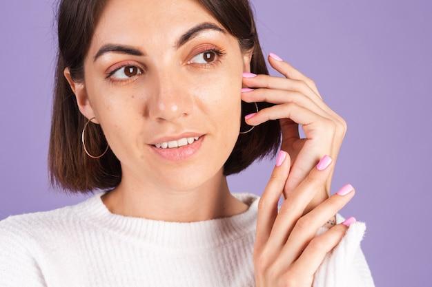 Koncepcja piękna paznokci, drobna kobieta z różowym wiosennym kolorem manicure biały sweter fioletowa ściana