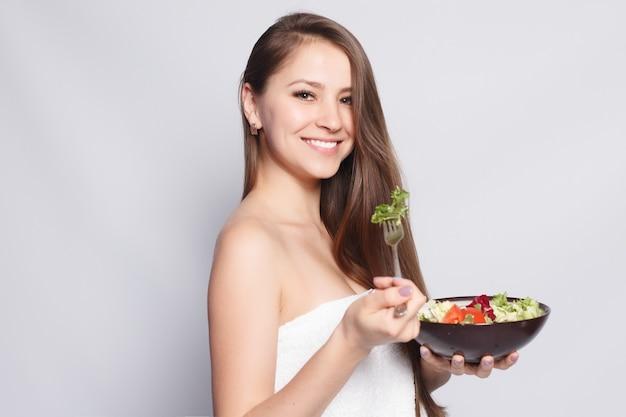 Koncepcja piękna, pielęgnacji skóry i ludzi - piękna brunetka dziewczyna w ręcznik jedzenie świeżej sałatki i uśmiechnięty. kobieta je jedzenie. piękna uśmiechnięta kobieta o na kolację świeżych warzyw w kuchni.