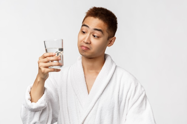 Koncepcja piękna, spa i technologii. niezły smak. portret zadowolony azjatykci mężczyzna w szlafroku sączy wodę od szkła i patrzeje zadowoloną kamerę, stoi biel ścianę
