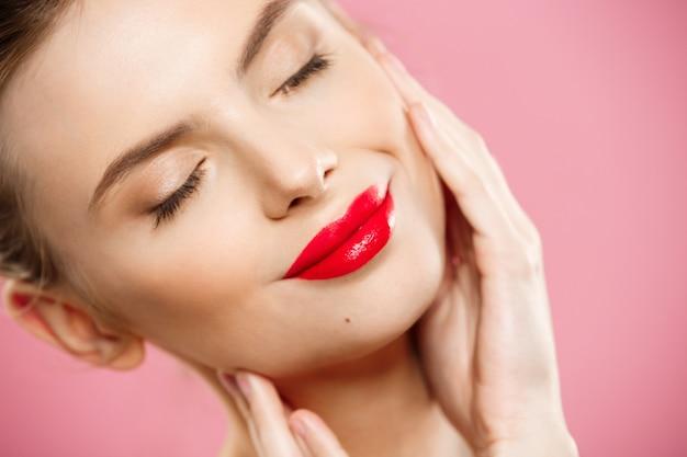 Koncepcja piękno - zamknij gorgeous młoda kobieta brunette portret twarzy. modelka piękna dziewczyna z jasnymi brwi, doskonałe makijaż, czerwone usta, dotykając jej twarzy. samodzielnie na tle różowy