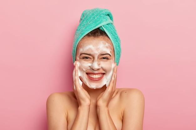 Koncepcja pielęgnacji i higieny. szczęśliwa młoda europejka masuje policzki, nakłada piankę bąbelkową, myje twarz, uśmiecha się pozytywnie, ma nagie ciało, lubi brać prysznic, chce mieć czystą skórę.