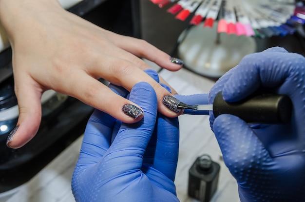 Koncepcja pielęgnacji paznokci manikiurzystka maluje paznokcie klientki zbliżenie