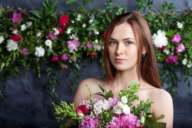 Koncepcja pielęgnacji skóry. dziewczyna o spokojnej twarzy stoi naga i trzyma kwiaty przed klatką piersiową. piękna kobieta z naturalnym makijażem czerpie przyjemność, trzymając bukiet