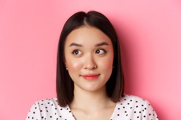 Koncepcja pielęgnacji skóry i piękna. zbliżenie: śliczna azjatycka nastolatka patrząc w lewo na baner, uśmiechnięta głupio, stojąca w sukience na różowym tle