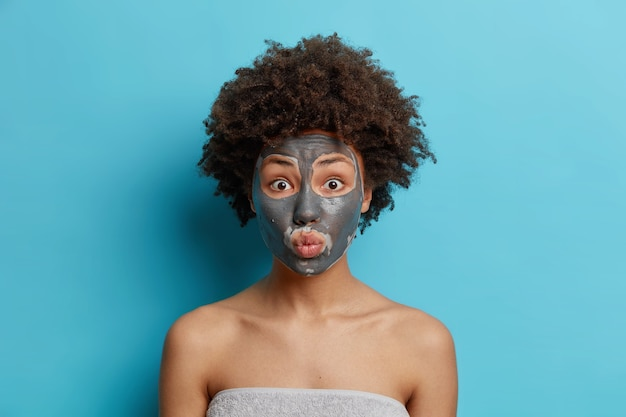 Koncepcja pielęgnacji skóry i urody. zdziwiona afroamerykanka z kręconymi włosami nakłada na twarz odżywczą maseczkę z glinki i cieszy się kuracją odtruwającą owinięta ręcznikiem kąpielowym pokazuje nagie ramiona odizolowane na niebiesko
