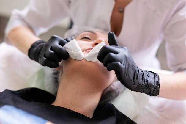 Koncepcja pielęgnacji skóry. kobieta w gabinecie kosmetycznym podczas zabiegu pielęgnacji skóry twarzy.