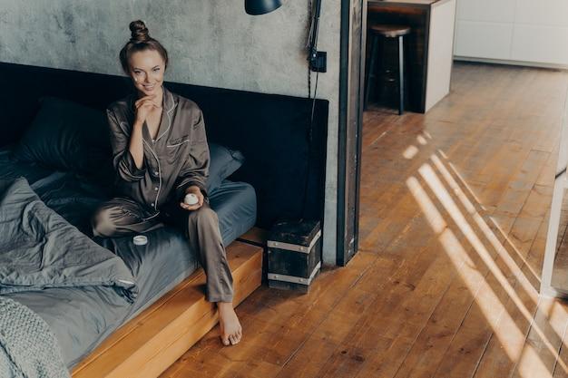Koncepcja pielęgnacji skóry. piękna uśmiechnięta młoda kobieta stosując nawilżający krem do twarzy podczas codziennych rutynowych zabiegów kosmetycznych, siedząc na łóżku po przebudzeniu się wczesnym rankiem w satynowej piżamie