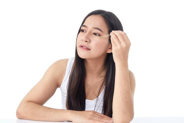 Koncepcja pielęgnacji skóry. piękno portret uśmiechnięta młoda azjatycka kobieta dziewczyna trzyma pipetę z olejkiem kosmetycznym lub serum w pobliżu czystej twarzy. kosmetologia i spa