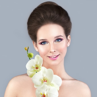 Koncepcja pielęgnacji skóry spa. zdrowa kobieta o jasnej skórze i białej orchidei