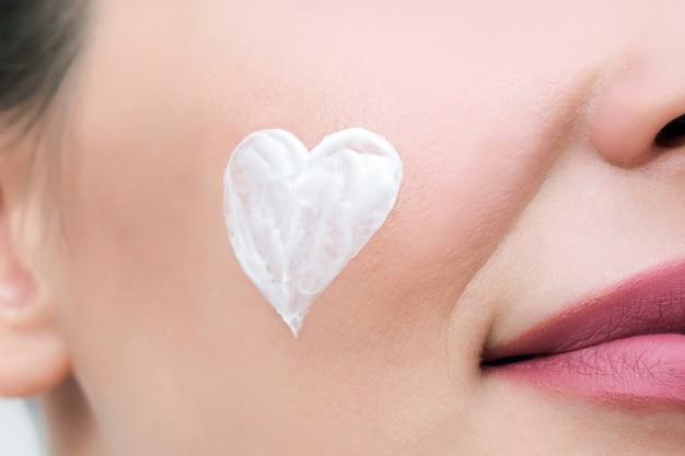 Koncepcja pielęgnacji skóry twarzy. młoda kobieta ma na twarzy kremowe serce.