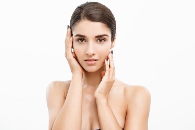 Koncepcja pielęgnacji skóry uroda. kaukaski kobieta dotyka jej na białym tle