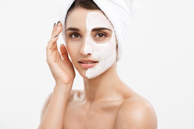 Koncepcja pielęgnacji skóry uroda - piękna twarz kobiety rasy kaukaskiej portret stosując maskę kremową na jej białej ścianie skóry twarzy.