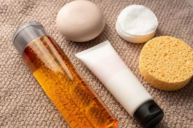 Koncepcja pielęgnacji twarzy. śmietanka, kostka mydła, gąbka, waciki i ślady na ręczniku.