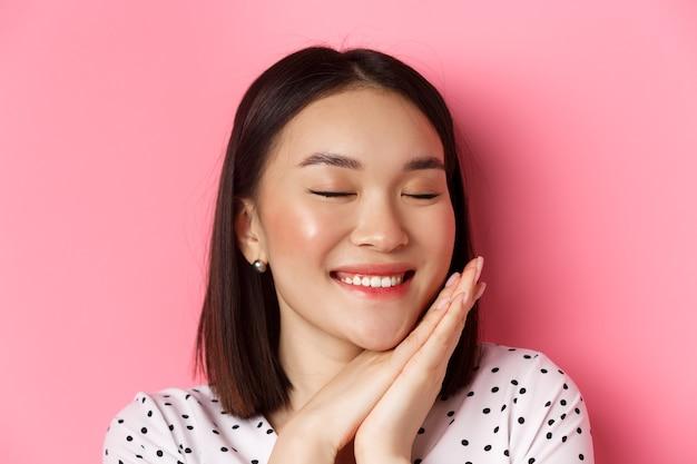 Koncepcja pielęgnacji urody i skóry. headshot uroczej i marzycielskiej azjatyckiej kobiety zamykającej oczy, uśmiechającej się nostalgicznie, stojącej na różowym tle