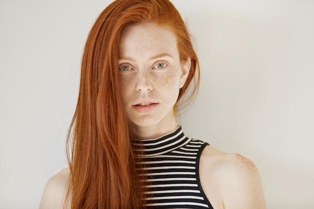 Koncepcja pielęgnacji urody i włosów. wspaniała młoda kaukaska rudowłosa kobieta z długą luźną fryzurą i piegami ubrana w pasiastą bluzkę bez rękawów, wyglądająca na zamyśloną i zamyśloną