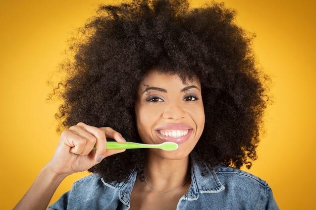 Koncepcja pielęgnacji zębów i higieny jamy ustnej. pozytywna młoda afroamerykańska kobieta z kędzierzawym ostrzyżeniem