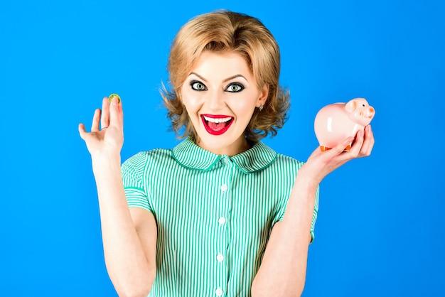 Koncepcja pieniądza bankowego pin up model z piggy bank w ręku seksowna zabawna retro moda dziewczyna w lecie